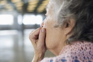 Close up of a depressed old woman