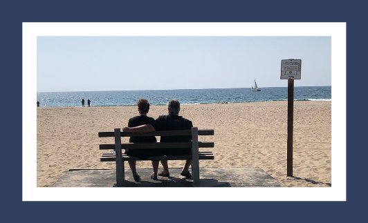 Two people sitting on a bench facing the beach